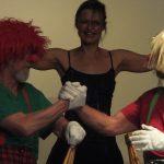 Bild von der Bühne einer Theater-Aufführung. Zwei Clowns sitzen einander gegenüber auf Stühlen schütteln sich die Hände, im Hintergund eine Person mit ausgestreckten Armen, die lacht.